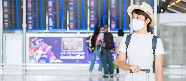 Młoda kobieta ubrana w maskę z bagażem sprawdzanie czasu lotu na lotnisku