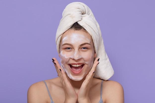 Młoda kobieta ubrana w maskę z hydro żelem, przy użyciu maseczki do twarzy, wygląda na szczęśliwą i podekscytowaną