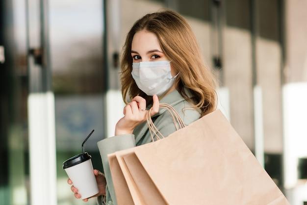 Młoda kobieta ubrana w maskę zapobiegającą wirusowi z torbami na zakupy na wąskiej uliczce w europie.