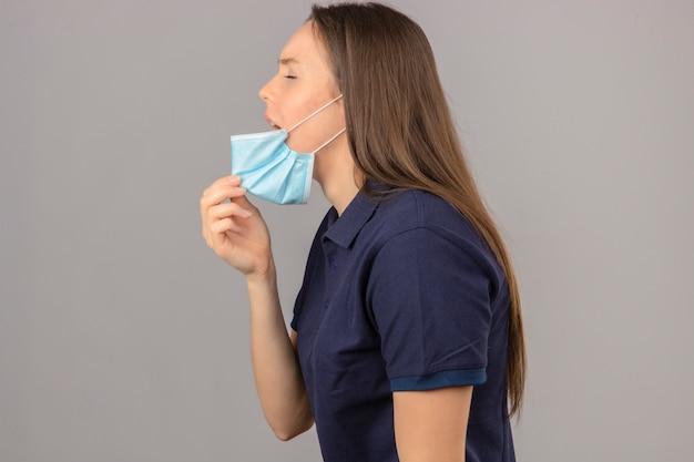 Młoda kobieta ubrana w niebieską koszulkę polo podnosząca maskę medyczną usta na kaszel, mdłości, stojąc na jasnoszarym na białym tle