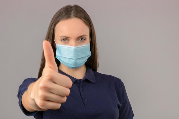 Młoda kobieta ubrana w niebieską koszulkę polo w ochronnej masce medycznej pokazując kciuk w górę pozytywny wyraz stojący na jasnoszarym tle