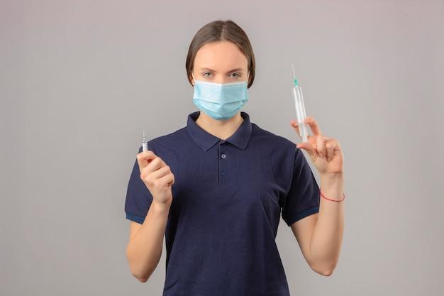 Młoda kobieta ubrana w niebieską koszulkę polo w ochronnej masce medycznej trzymając strzykawkę i butelkę szczepionki lekarskiej patrząc na kamerę z poważną twarzą stojącą na odizolowanym szarym tle