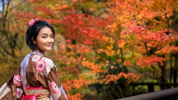 Młoda kobieta ubrana w niebieskie kimono i parasol wybrała się na spacer po parku w jesiennych liściach w japonii