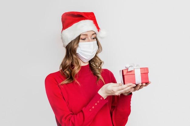 Młoda kobieta ubrana w ochronną medyczną maskę na twarz i santa hat trzyma czerwone pudełko na białym tle na szarym tle studio. prezenty noworoczne podczas koncepcji koronawirusa kwarantanny. zamówienie online