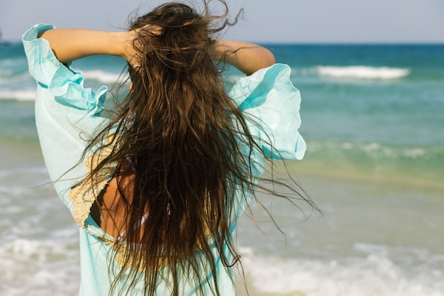 Młoda kobieta ubrana w piękny niebieski strój idzie nad brzegiem morza