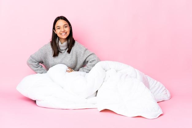 Młoda kobieta ubrana w pijamę siedzi na podłodze, pozowanie z rękami na biodrze i uśmiechnięty