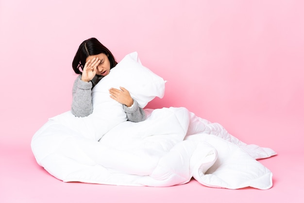 Młoda kobieta ubrana w pijamę siedzi na podłodze z wyrazem zmęczony i chory