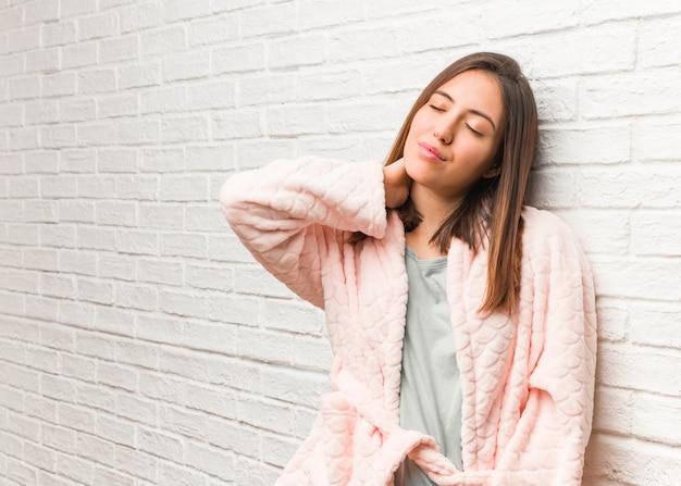 Młoda kobieta ubrana w piżamę cierpi ból szyi
