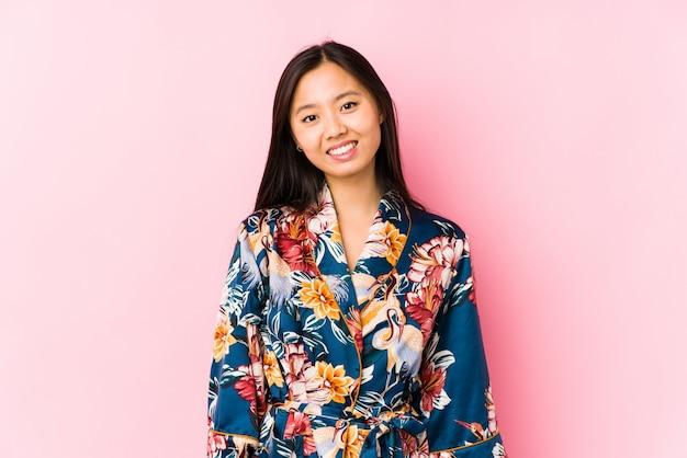 Młoda kobieta ubrana w piżamę kimono szczęśliwa, uśmiechnięta i wesoła.