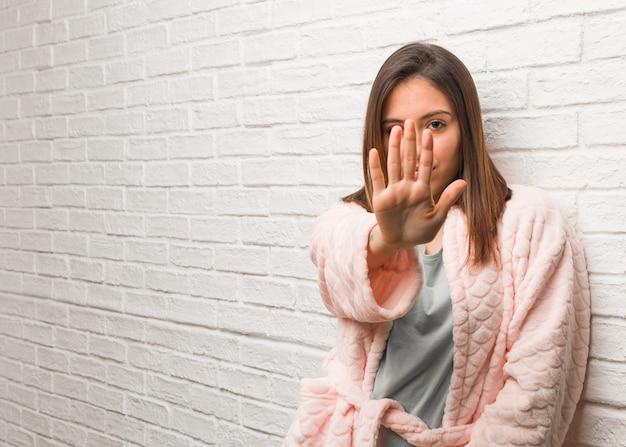 Młoda kobieta ubrana w piżamę kładąc rękę z przodu
