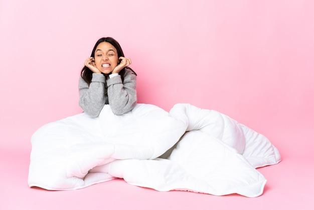 Młoda kobieta ubrana w piżamę siedzi na podłodze sfrustrowana i zakrywająca uszy