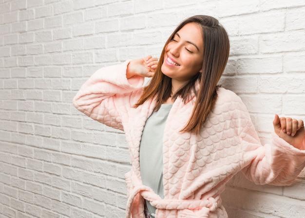 Młoda kobieta ubrana w piżamę, taniec i zabawę