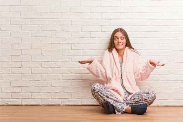Młoda kobieta ubrana w piżamę zmieszana i wątpliwa