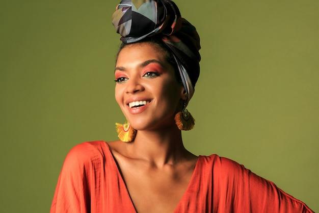 Młoda kobieta ubrana w pomarańczową sukienkę z turbanem i biżuterią etniczną