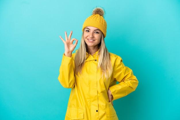 Młoda kobieta ubrana w przeciwdeszczowy płaszcz na odosobnionym niebieskim tle pokazującym znak ok palcami