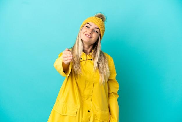Młoda kobieta ubrana w przeciwdeszczowy płaszcz na odosobnionym niebieskim tle, ściskając ręce, aby zamknąć dobrą ofertę