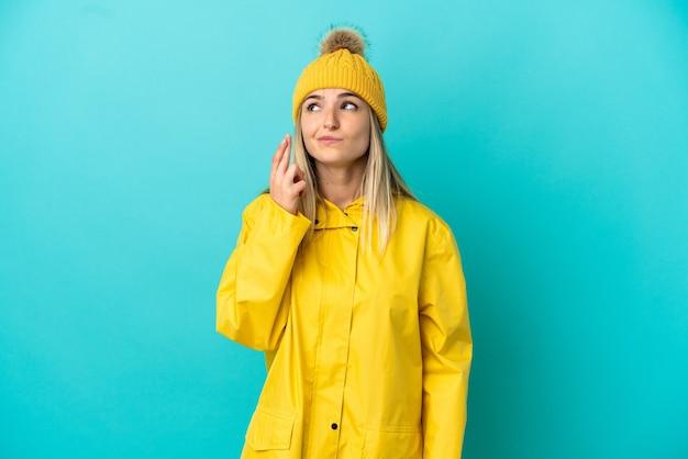 Młoda kobieta ubrana w przeciwdeszczowy płaszcz na odosobnionym niebieskim tle z palcami skrzyżowanymi i życzącymi wszystkiego najlepszego