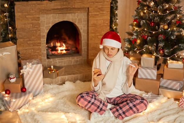 Młoda kobieta ubrana w santa hat, szalik i spodnie w kratkę