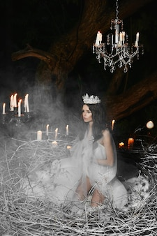 Młoda kobieta ubrana w satynową bieliznę pozuje w wielkim gnieździe ze świecami na tle
