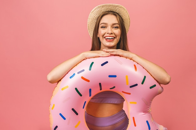 Młoda kobieta ubrana w strój kąpielowy, skoki i trzymając nadmuchiwany pierścień pływać