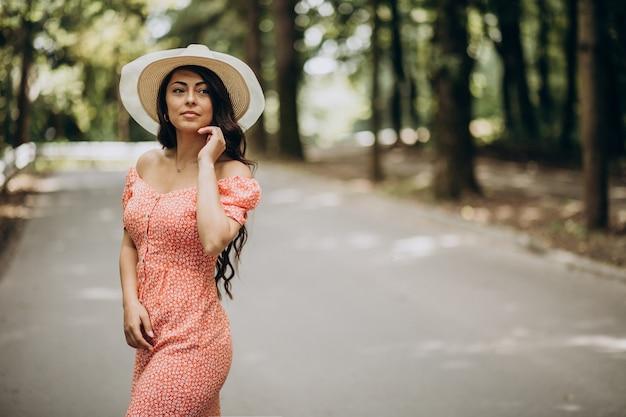 Młoda kobieta ubrana w sukienkę i kapelusz spaceru w parku