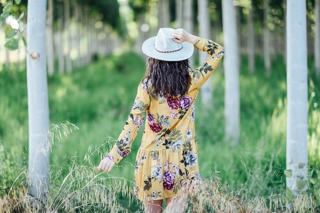 Młoda kobieta, ubrana w sukienkę w kwiaty, między drzewami.