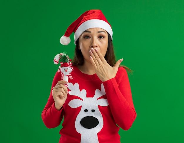Młoda kobieta ubrana w świąteczny santa hat i czerwony sweter trzymający bożonarodzeniową trzcinę cukrową, która jest zszokowana, zakrywając usta ręką stojącą nad zieloną ścianą