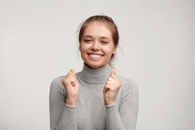 Młoda kobieta ubrana w szary golf