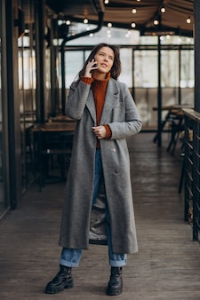 Młoda kobieta, ubrana w szary płaszcz i chodzenie po ulicy i korzystanie z telefonu