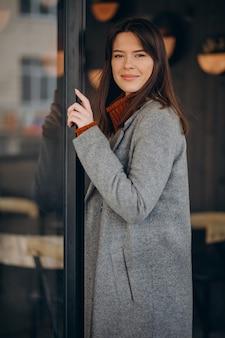 Młoda kobieta, ubrana w szary płaszcz i spacerująca po ulicy
