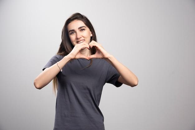 Młoda kobieta ubrana w szary t-shirt na szarym tle robi kształt symbolu serca rękami.