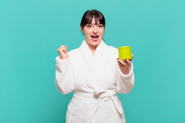 Młoda kobieta ubrana w szlafrok jest zszokowana, podekscytowana i szczęśliwa, śmiejąc się i świętując sukces, mówiąc wow!