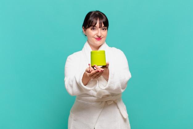 Młoda kobieta ubrana w szlafrok, uśmiechnięta radośnie z przyjaznym, pewnym siebie, pozytywnym spojrzeniem, oferująca i pokazująca przedmiot lub koncepcję