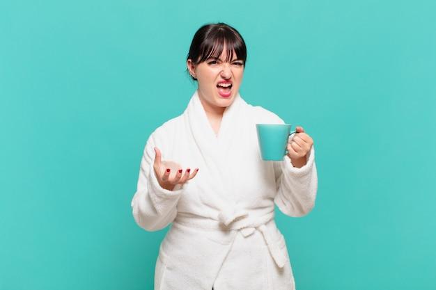 Młoda kobieta ubrana w szlafrok wygląda na złą, zirytowaną i sfrustrowaną, krzycząc wtf lub co jest z tobą nie tak