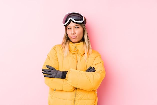 Młoda kobieta ubrana w ubrania narciarskie w różowej ścianie niezadowolony patrząc z przodu z sarkastycznym wyrazem twarzy