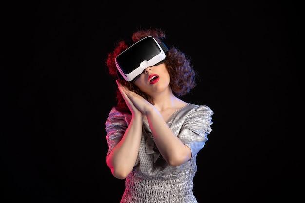 Młoda kobieta ubrana w zestaw słuchawkowy wirtualnej rzeczywistości na ciemnej powierzchni