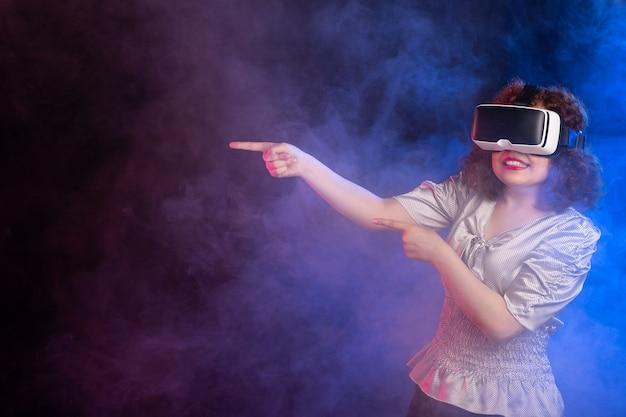 Młoda kobieta ubrana w zestaw słuchawkowy wirtualnej rzeczywistości na ciemnoniebieskiej powierzchni
