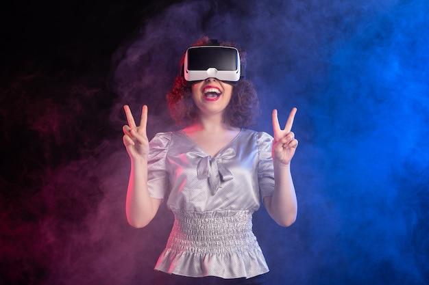 Młoda kobieta ubrana w zestaw słuchawkowy wirtualnej rzeczywistości na ciemnym bluesurface