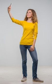Młoda kobieta ubrana w żółtą koszulę i dżinsowe szorty rozmawia z telefonem i robi miny na szarym tle