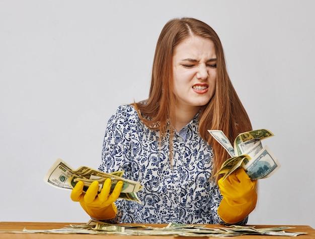Młoda kobieta ubrana w żółte gumowe rękawiczki i patrząc na dolary z obrzydzeniem