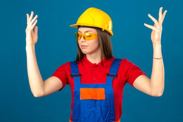 Młoda kobieta ubrana w żółte okulary w mundurze budowy i żółty kask stojący z zamkniętymi oczami i uniesionymi rękami na niebieskim tle
