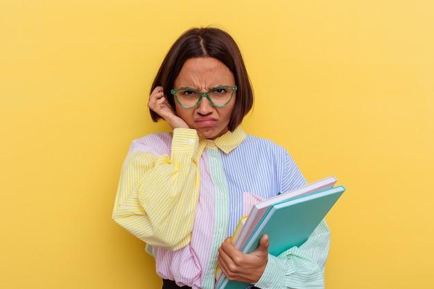 Młoda kobieta uczeń rasy mieszanej na białym tle na żółtym tle obejmujące uszy rękami.