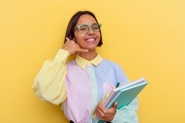 Młoda kobieta uczeń rasy mieszanej na białym tle na żółtym tle pokazując gest połączenia telefonu komórkowego palcami.