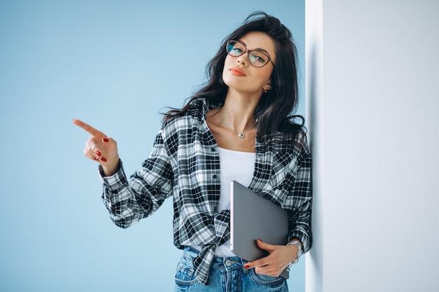 Młoda kobieta uczeń z laptopem przy biurem