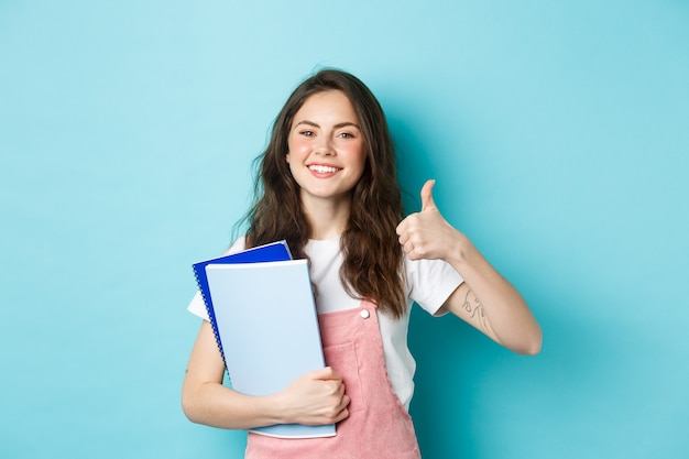 Młoda kobieta uczęszcza na kursy, studentka studiująca, trzymająca zeszyty i pokazująca kciuk z aprobatą, polecająca firmę, stojąca na niebieskim tle