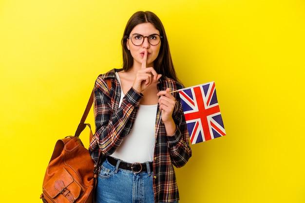 Młoda kobieta uczy angielskiego na białym tle na różowej ścianie, zachowując tajemnicę lub prosząc o ciszę