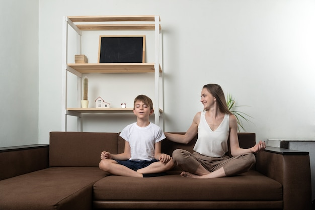 Młoda kobieta uczy chłopca medytować siedząc na kanapie. joga w domu z dziećmi.