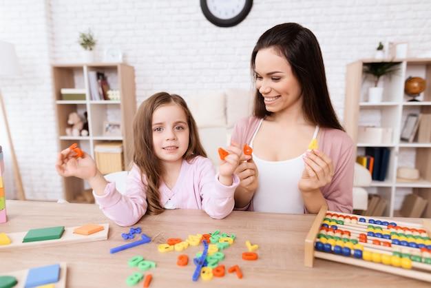 Młoda kobieta uczy małej dziewczynki matematyki na drewnianym abakusie.