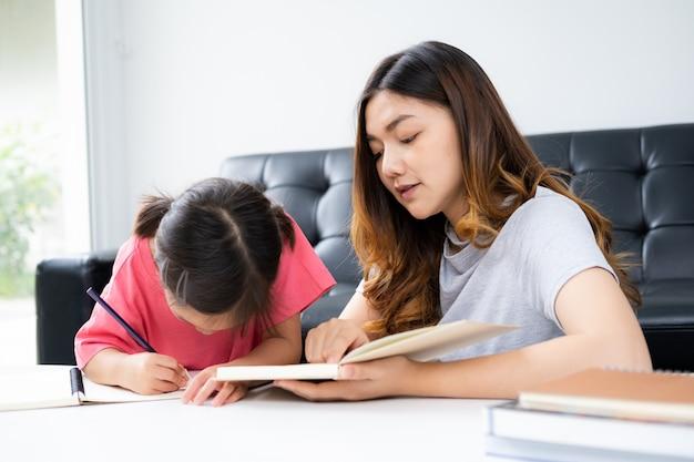 Młoda kobieta uczy pracę domową swojego dziecka w domu
