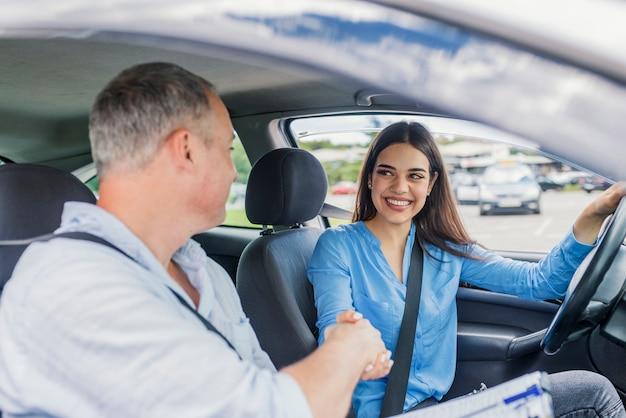 Młoda kobieta uczy się jeździć samochodem wraz z jej instruktorem.